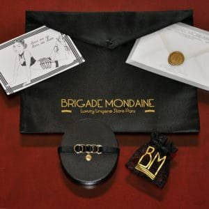 Ici vous pouvez voir le Pack cadeau luxe de la marque Brigade Mondaine. Dedans il y a un chocker noir avec sa pochette et une carte signée et dédicacée juste pour vous. Tout cela est contenu dans une pochette en soie noire.