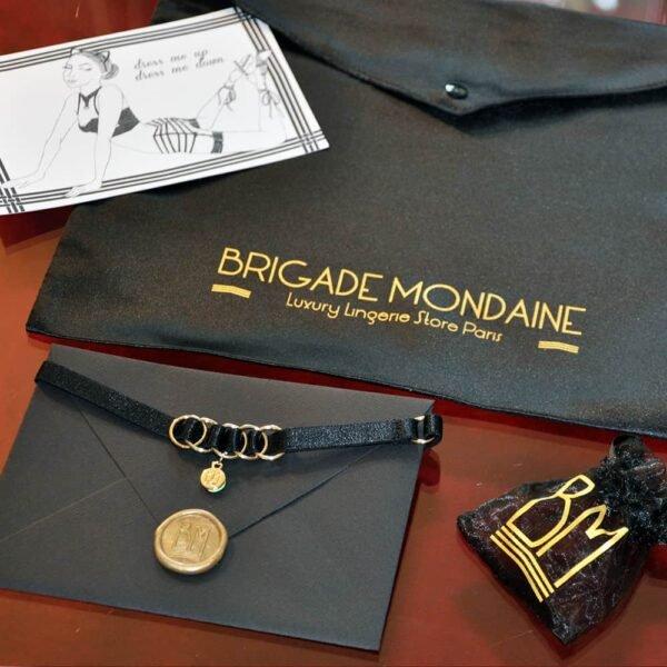 Aquí puedes ver el paquete de regalo de lujo de Brigade Mondaine. En el interior hay un chocker negro con una bolsa y una tarjeta firmada sólo para ti. Todo ello está contenido en una bolsa de seda negra.