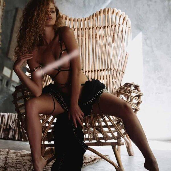 Playsuit Agnès de la marque Couture de nuit inspirés du bondage. Le produit est confectionné d'élastiques en velours couleur olive et de curseurs et anneaux en plaqué or. La forme du produit enveloppe les deux seins et se recroisent sur un anneau central placé au nombril qui repartent jusqu'aux hanches. Deux maintiens dorsaux sont présents, l'un sur le milieu du dos et l'autre sur le haut du fessiers. Deux tours de jambes sont également reliés à l'ensemble.