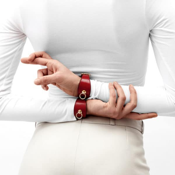 Linotte red bdsm leather bracelet with ring and gold finishes by Domestique at Brigade Mondaine
