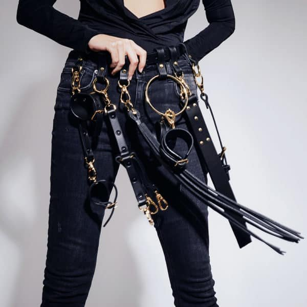 Black leather belt with multiple gold ELF ZHOU attachments at Brigade Mondaine