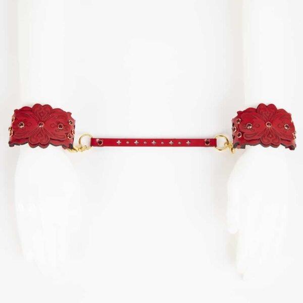 Красные наручники из гравированной кожи с золотой отделкой и мелкими кристаллами из коллекции Original Rosso с автографом Fraulein Kink на выставке Brigade Mondaine.
