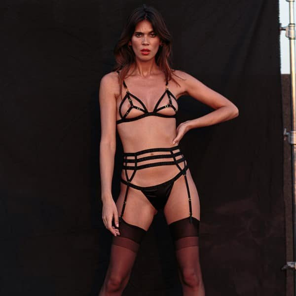 The model is wearing a bra from the brand Atelier Amour. This bra is made of satin and elastic, it forms a cross on each breast with the elastics.