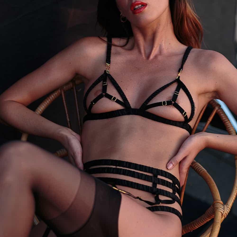 La modelo lleva un sujetador de la marca Atelier Amour. Este sujetador es de raso y elástico, forma una cruz en cada pecho con los elásticos.