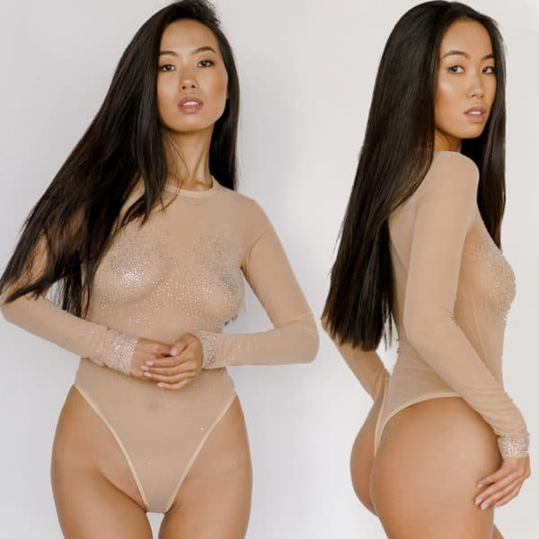 Bodysuit Air from the brand Crystal Eyez. This bodysuit is cream in a transparent illusion mesh. The product is a long sleeve bodysuit with Swarovski rhinestones on the chest and sleeve ends.