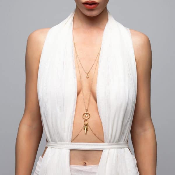 Jewel of a backless and crossed body on the bust with gold feathers falling on the belly