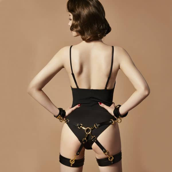 Black leather bondage accessories, handcuffs and link with gold details UPKO at Brigade Mondaine