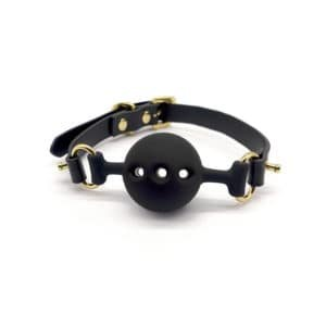 Black leather and silicone baillon in the shape of a ball with holes for breathing, gold finish UPKO at Brigade Mondaine