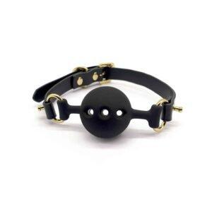Baillon de cuero negro y silicona en forma de bola con agujeros para respirar, acabado dorado UPKO en Brigade Mondaine