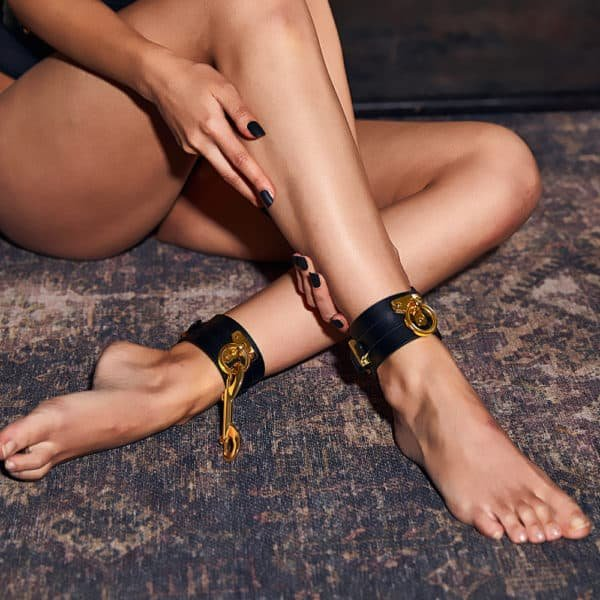 black leather ankle cuffs with gold details and fasteners