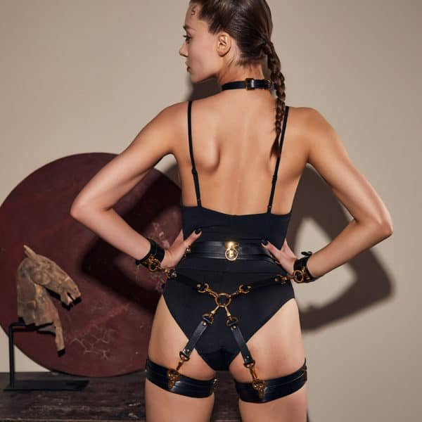 Black leather handcuffs attached to a black harness at the buttocks and hips with gold details. Black leather garters are attached to the harness.