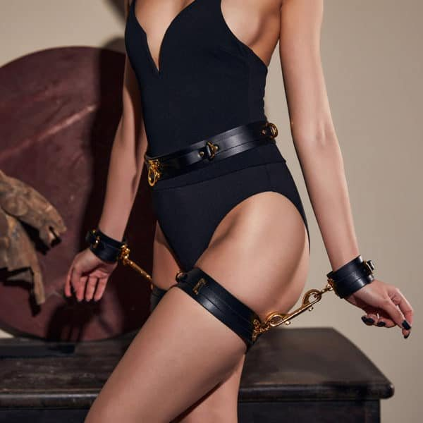 Black leather handcuffs with gold details, the handcuffs are attached to black leather garters