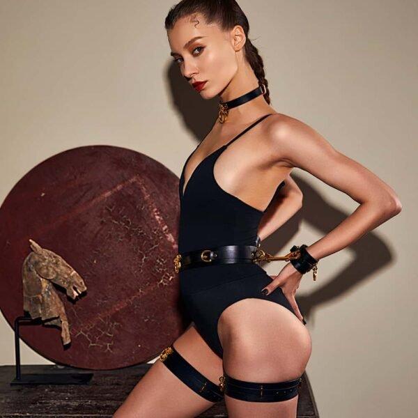 Черные кожаные наручники с золотыми деталями, наручники крепятся на кожаный ремешок вокруг талии, подвязочные ремни сделаны из черной кожи.