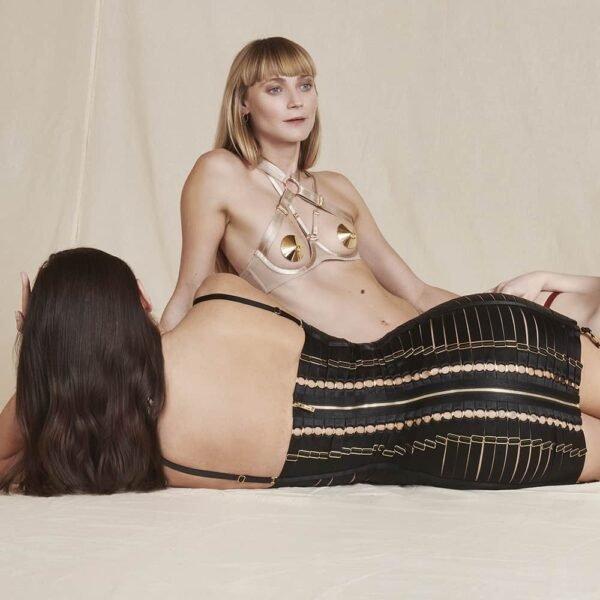 Robe Angela noire de la marque Bordelle. Ce produit est composé de plus de cent cinquante élastiques en satin et de fermoir, réglages, porte jarretelles et une fermeture plaqués en or 24 carats. La robe est confectionné d'une accumulation d'élastiques qui moule le corps et d'elastiques qui imitent la forme d'un harnais. Pour le derrière, un zip est présent tout le long de la robe avec des anneaux de part et d'autre de la fermeture pour un effet corseté.