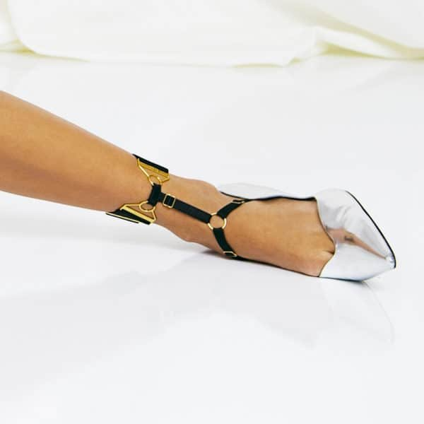 Wide Strap ankle harness from Bordelle. This harness is made of a very comfortable satin elastic band. One part is made with transparent fishnet and the 24 carat gold finishings come to sublimate the whole.