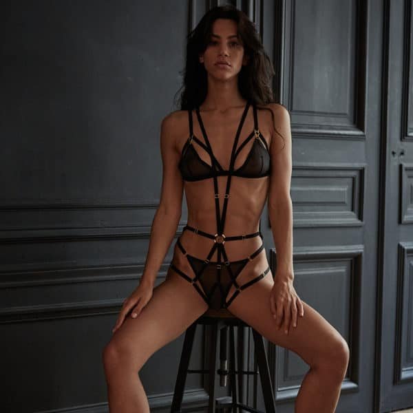 Black elastic and fishnet harness set with tulle bra and black elastic and black tulle high pants from the Unbearable Lightness collection d'Atelier Amour at Brigade Mondaine