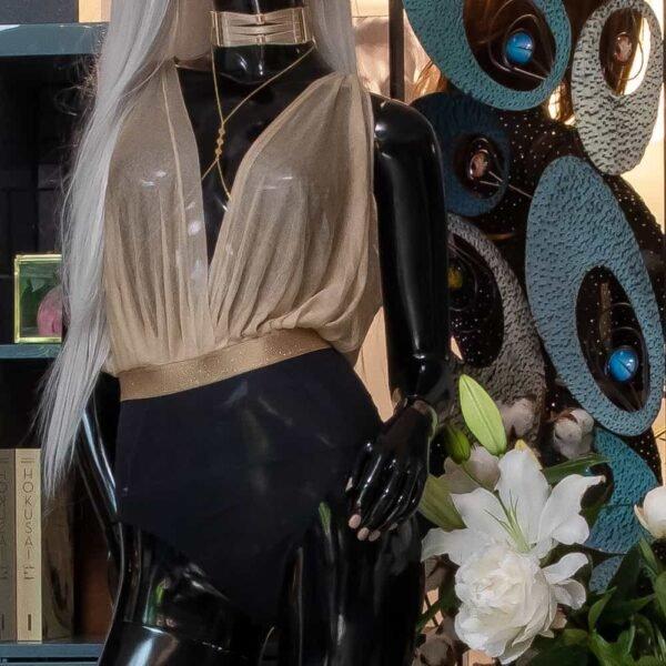 Модель одета в черно-золотой боди-комбинезон Gonzales Affaires из шелкового тюля и атласной резинки. Низ боди-комбинезона черный, трусики с высокой талией, бюст золотистого цвета с глубоким V-образным вырезом.