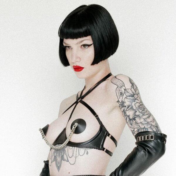 Soutien-gorge cuir liquorice de la marque ELF ZHOU LONDON. La partie qui passe sous les seins du modèle est en cuir noir, le soutien-gorge est ouvert sur la zone des seins. Il y a trois bandes qui découpent le haut du soutien-gorge : une qui passe entre les seins et deux autres qui partent sur la diagonale et rejoignent l'arrière. Elle porte des nippies noirs et tous deux reliés par une chaine en argent. On peut percevoir les tatouages du modèle.