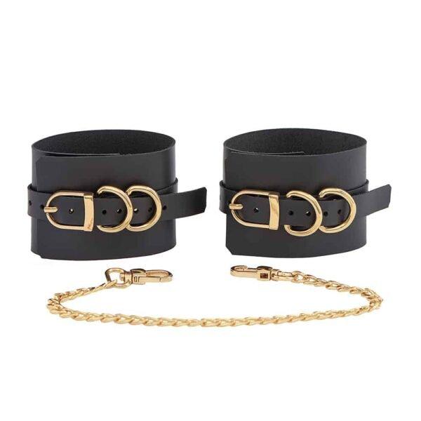 Регулируемые черные кожаные наручники SENSUALITY ANKLE CUFFS с металлической отделкой из золота от MIA ATELIER на выставке BRIGADE MONDAINE.