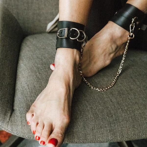 Регулируемые черные кожаные манжеты из черной кожи ANKLE CUFFS с золотисто-металлической отделкой от MIA ATELIER в BRIGADE MONDAINE