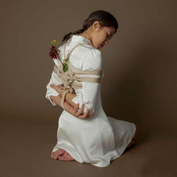 Cuerda de Shibari de color crema de la marca UPKO. El maniquí lleva una cuerda entrelazada de 10 m de longitud y 6 mm de diámetro.