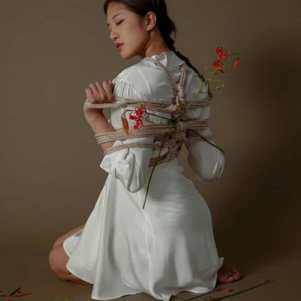 Веревка Шибари кремового цвета от бренда UPKO. На манекен надета переплетенная веревка длиной 10 м и диаметром 6 мм.