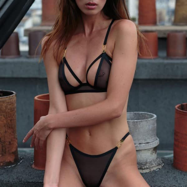 The model is wearing a bra of the brand Atelier Amour made of tulle and black satin elastic. This bra is half open at the chest.