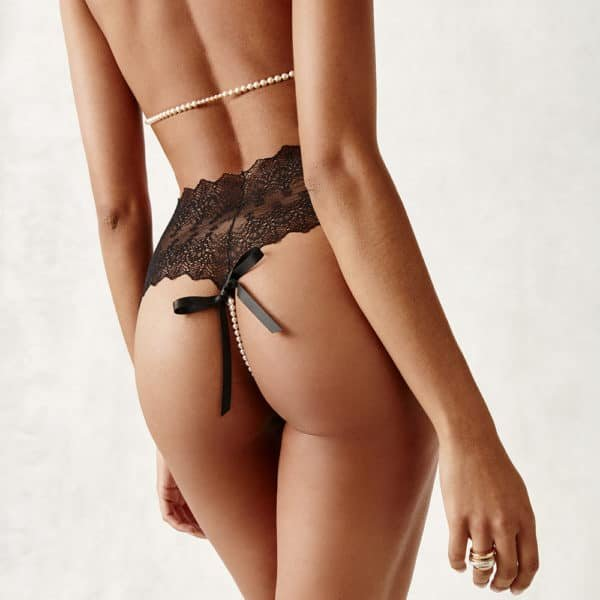 Transparent black PANTY g-string made of lace and pearls from Majorca taken from the back with a silk bow. From the BRACLI brand GENEVA collection at BRIGADE MONDAINE