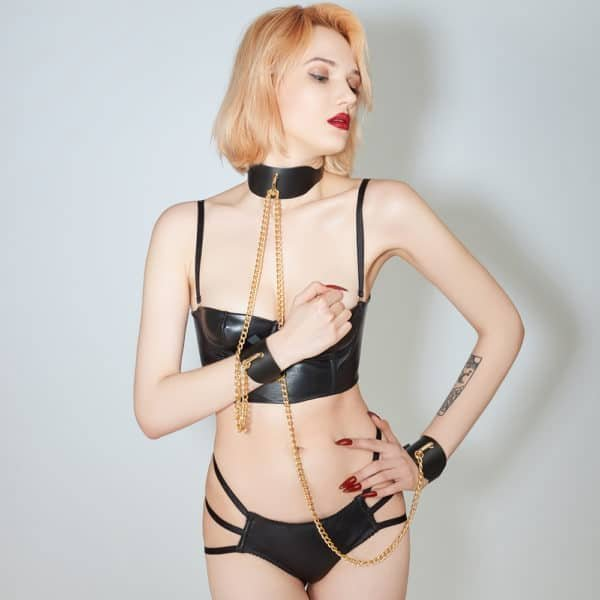 Pair of black vegetal leather handcuffs and black vegetal leather necklace 24k gold plated chain worn on a model wearing a ELF Zhou London Signature Black Liquorice panty and black leather bustier from ELF Zhou London at Brigade Mondaine