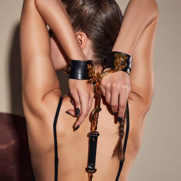 black leather handcuffs with gold details and ties, all attached to a leash