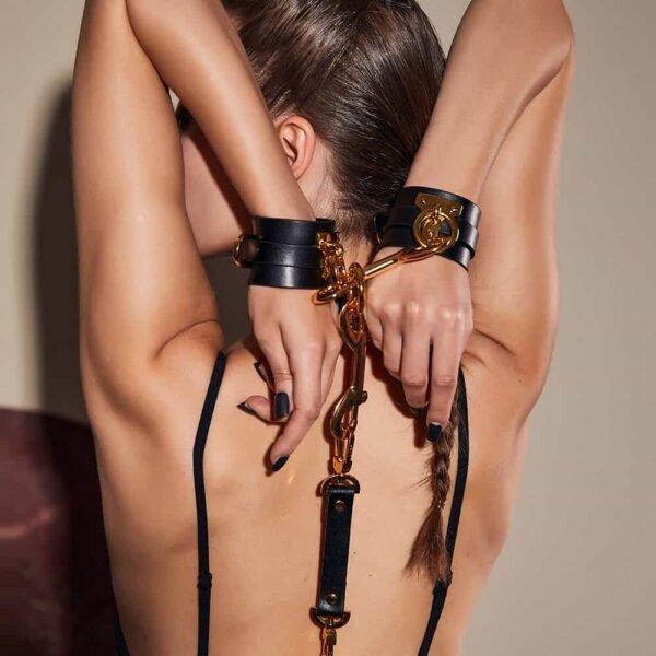 Esposas de cuero negro con detalles y lazos dorados, todo ello unido a una correa