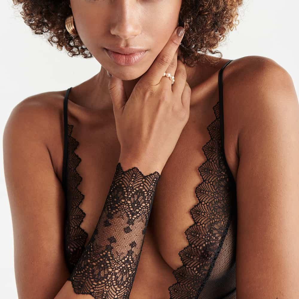 Geneva black lace V-neck bodystocking and Geneva black lace gauntlet in close-up view worn on a white background model from the Geneva collection by Bracli at Brigade Mondaine