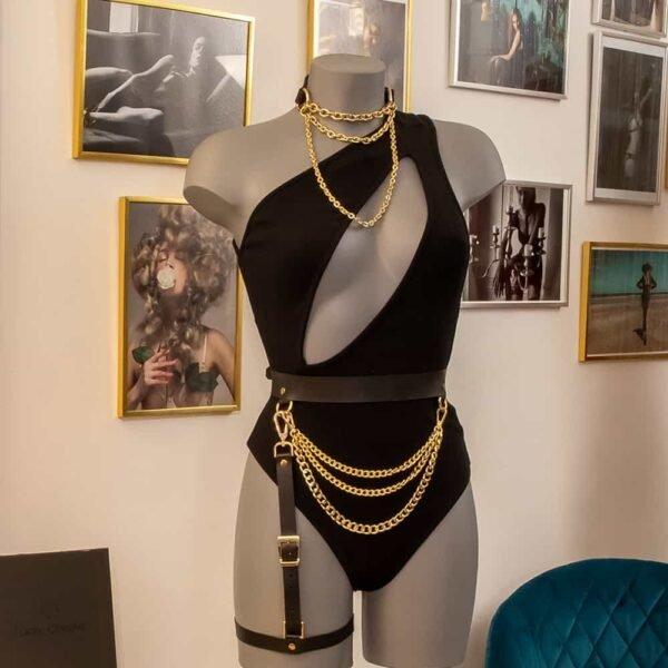 Nous pouvons voir un mannequin portant le body Nadine de chez Ow Intimates, il est noir et possède une fente allant du coup au dessous de la poitrine en diagonale. Il porte aussi un chocker bondage Elif Domanic en couleur or. Ainsi qu'une ceinture jarretière cuir de chez Mia Atelier en noir et or.