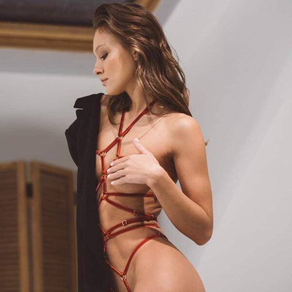 Playsuit Gia rojo de la marca Couture de nuit inspirado en el bondage. El producto está fabricado con elásticos de terciopelo negro y deslizadores y anillos chapados en oro. Una multitud de cruces forman la parte delantera del producto con doce anillos que trazan el recorrido del elástico. El producto se sujeta en el cuello y también contiene dos elásticos traseros colocados en la parte media y superior de las nalgas. Para los glúteos, los elásticos se colocan a los lados formando un tanga con un anillo colocado en la parte superior de los glúteos y redistribuyendo dos pequeños elásticos.