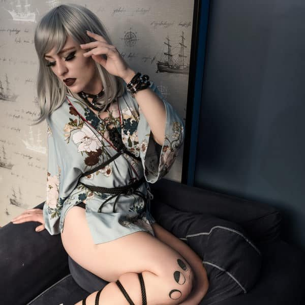 Harness with black rope collar, tightened at the waist and silver details on a blue floral kimono