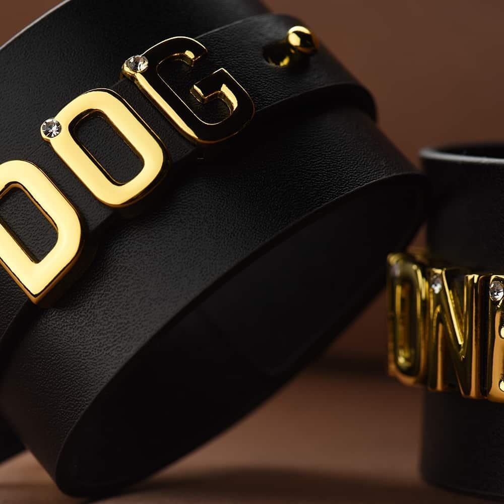 Наручники для запястий из черной итальянской кожи крупным планом с изображением слова DOG с 24-каратными позолоченными буквами с инкрустациями камней в каждой букве, используемыми в качестве идеи для сотрудничества UPKO X Brigade Mondaine.