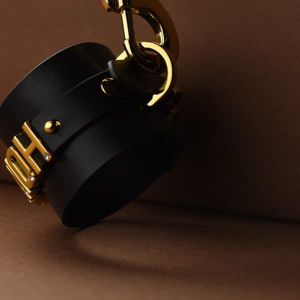 Close-up view of d'an Italian black leather handcuff with 24 carat gold-plated and engraved by the brand UPKO for l'limited edition UPKO X Brigade Mondaine at Brigade Mondaine