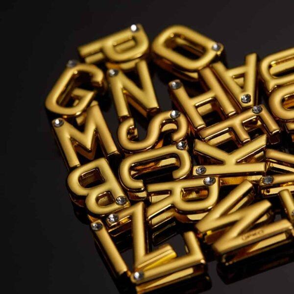 Conjunto de letras utilizadas para esposas y cuellos en cuero negro italiano y colgadores de oro de 24 quilates de la colaboración UPKO X Brigade Mondaine ensamblados y disponibles en Brigade Mondaine