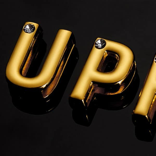 Letter U and P in 24 karat gold-plated inlaid with small brilliant stones presented on a black background seen very closely for the collaboration UPKO X Brigade Mondaine at Brigade Mondaine