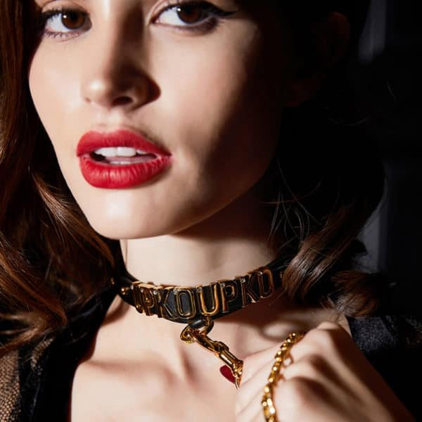 Necklace with UPKOUPKO markings in gold lettering and 24 carat gold-plated ring worn around the neck d'a mannequin and in close-up view attached to a leash that d'inspiration for the products of the collaboration UPKO X Brigade Mondaine