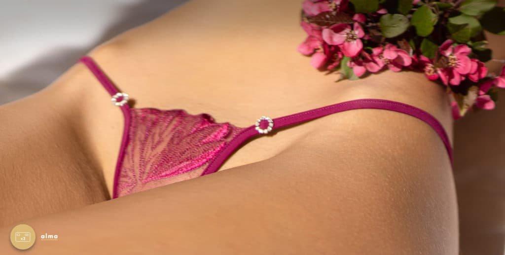 Le modèle porte un string de la marque Lucky Cheeks. Coffret String Bijou Purple Temptation, String violet en dentelle transparente avec ficelle rehaussée de deux anneaux en strass de Swarovski.