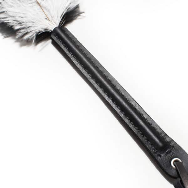 plumas de avestruz blancas y negras sobre mango de cuero negro, el objeto entero mide 45 cm y las plumas 25 cm