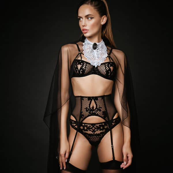 Very sexy judge's outfit with many details in fishnet or black patterns. The bras reveal the breasts thanks to a few openings, the suspender belt goes up high on the belly and tightens the waist, the g-string is black with motifs and fishnet at the front, the collar is made of white lace with black jewelry and finally it has a light transparent cape falling down at the back.