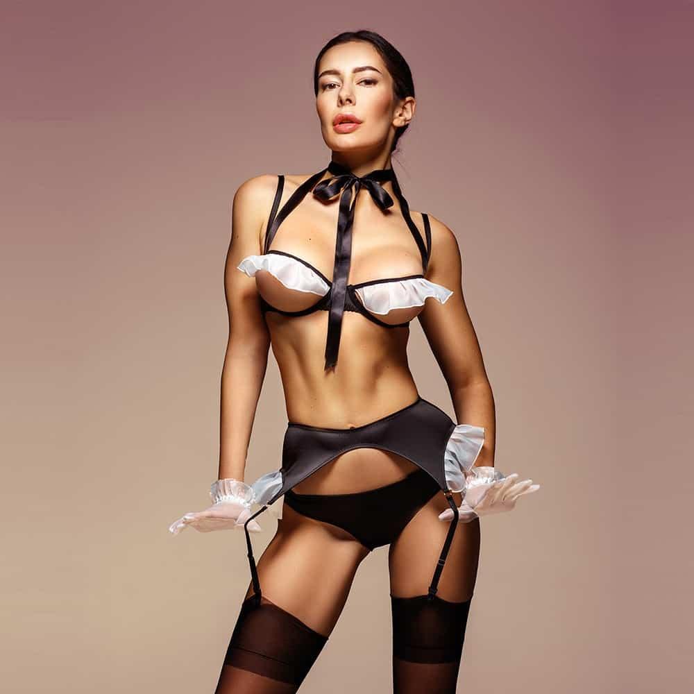 Sexy disfraz de sirvienta negra con volantes blancos en los pechos y las caderas. Se compone de un sujetador abierto que deja ver los pechos, un lazo alrededor del cuello, un liguero negro y unas bragas negras.