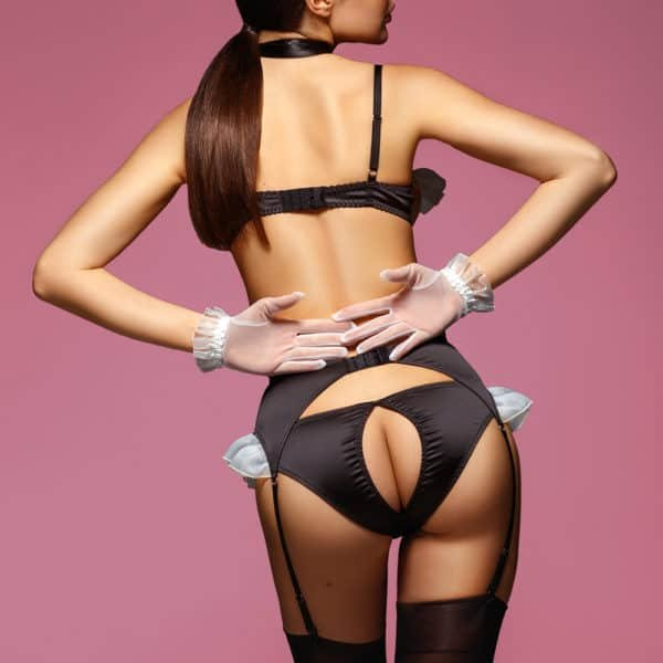 Sexy black maid costume with white flounces on the breasts and hips. It is composed of d' an open bra letting appear the breasts, a knot around the neck, a black suspender belt and black panties open on the buttocks.