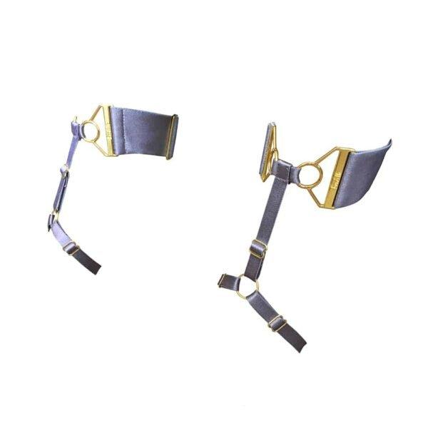 Tobilleras Tundra lila de la marca Bordelle. Este producto está fabricado con un elástico lila y mosquetones, anillas y ajustes chapados en oro. La correa del tobillo es un grueso elástico lila con un ajuste dorado en la parte delantera. También hay una correa en el arco del pie con un anillo en la parte superior del pie. Una fina cinta elástica une las dos bandas elásticas y viste el pie.