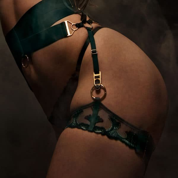 Green suspender belt Eden collection Aurea of the brand BORDELLE. This Suspender Belt emphasizes the waist with two wide bands in the center of which is a golden ring. At the front and at the back a third band joins a side ring on each side of the hips. These bands are connected to this ring by a gold-plated snap hook. To this same ring are also connected the bands leading to the garter and to the waist of the garter belt. This garter belt is adjustable at the waist with adjustment buckles. In addition, it opens at the back with a zipper.