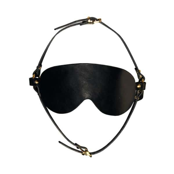 Arien BDSM blinding mask from Elif Domanic. This mask is entirely made of black leather and has a thick bezel with a headband decorated with nails. Another headband from the skull to the chin, also in black leather, is attached by a thin loop at the chin. The whole is linked by two rings placed at the ears.