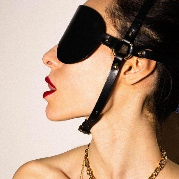 Masque aveuglant BDSM Arien de la marque Elif Domanic. Ce masque est entièrement en cuir noir et comporte une lunette épaisse avec un tour de tête orné de clous. À cela s'ajoute un autre tour de tête allant du crâne au menton, toujours en cuir noir qui s'attache par une fine boucle au niveau du menton. L'ensemble est relié par deux anneaux placés aux oreilles.