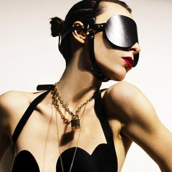 Ослепительная маска Ариен BDSM от Элиф Доманик. Эта маска полностью сделана из черной кожи и имеет толстый безель с оголовьем, украшенным ногтями. Другое оголовье от черепа до подбородка, также выполненное из черной кожи, крепится на подбородке тонкой петлей. Все это связано двумя кольцами, расположенными на ушах.